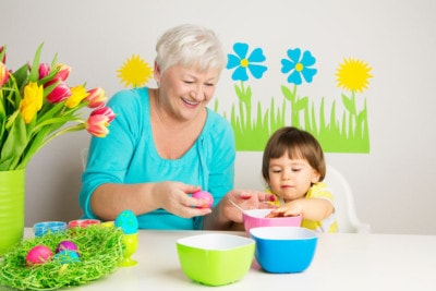 25236392 - happy grandmom and grandson color eggs for easter at home
