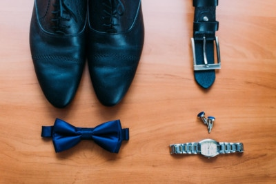 57551159 - close up of modern man accessories. dark blue bowtie, leather shoes, belt, watch and cufflinks isolated on wood rustic background.